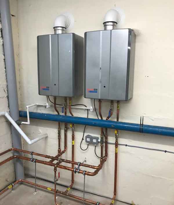 commercial gas boiler installation with 2 boilers mounted on wall